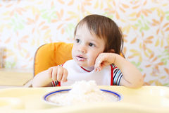 Wistful baby eating quark Stock Image