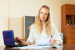Wistful blonde woman working with financial documents Royalty Free Stock Photo