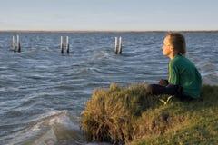 Wistful Boy on lake  Royalty Free Stock Photos