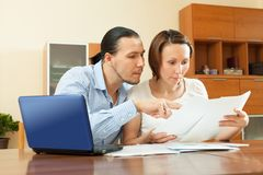 Wistful couple calculating budget at home interior Royalty Free Stock Photo