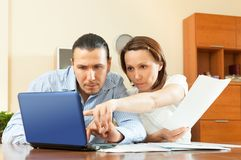 Wistful couple calculating something at home interior Stock Photography