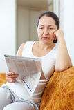 Wistful mature woman looks newspaper Royalty Free Stock Photo