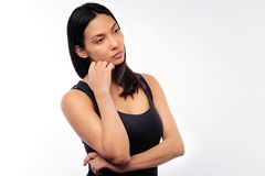 Beautiful woman being deep in thought. Wistful mood. Beautiful black-haired young woman in a black tank top resting her face on hand while being deep in thought Stock Photo