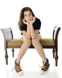 Wistful Tween. A pretty preteen girl wistfully sitting on a bench with her head propped by her hands, knees together and feet spread apart.  She's wearing shorts Royalty Free Stock Photography