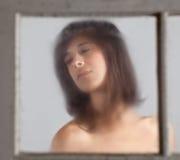 Wistful Woman Through Foggy Window Stock Image