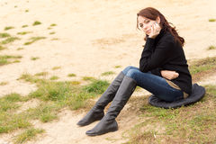 Wistful young woman sitting outdoors alone. On a cushion on sandy ground looking at the ground with a sombre expression as she rests her chin on her hand Stock Images