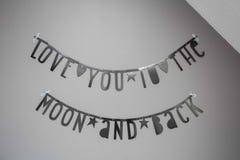 Wiszące dekoracyjne flagi z wpisową miłością ty księżyc plecy i, literowanie dekoracja, siwiejesz ścianę jako tło tekst zdjęcia stock