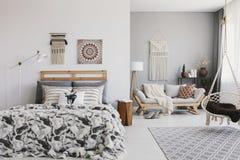 Wiszący krzesło nad dywan w przestronnym boho mieszkania wnętrzu z plakatem nad łóżko zdjęcie stock