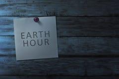 Wiszący nutowy papier z ziemską godziny wiadomością na drewnianej ścianie Obraz Stock