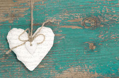Wiszący serce i turkusowy drewniany tło w kraju stylu.