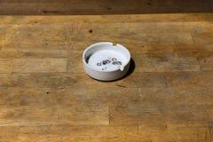 Wit asbakje op houten lijst Royalty-vrije Stock Afbeelding