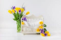 Wit babybed voor een pasgeboren kind op een witte achtergrond, die met gele tulpen en purpere irissen wordt verfraaid stock fotografie