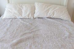 Wit bed en dubbel die hoofdkussen door slordige wol wordt behandeld stock foto