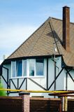 Wit buitenhuis met een mooie afwerking met bruine houten latjes royalty-vrije stock afbeelding