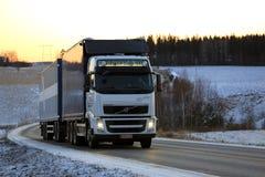 Wit de Combinatievoertuig van Volvo FH op de Weg van de de Winterzonsondergang Royalty-vrije Stock Foto