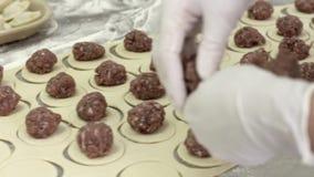 Wit de omslagvlees van vrouwenarbeiders in deeg voor bollen Het werk van de vleesfabriek stock video