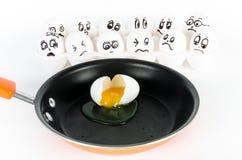 Wit die ei in koekepan met eieren met doen schrikken gezichten wordt gebroken Royalty-vrije Stock Foto