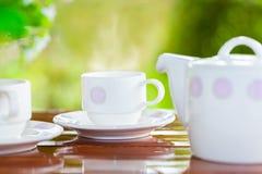 Wit die porselein voor thee of koffie op houten lijst wordt geplaatst stock afbeelding