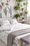 Wit en groen organisch linnen en grijze woldeken op een bed in een helder slaapkamer binnenlands hoogtepunt van installaties stock afbeeldingen