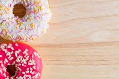Wit en roze donuts op houten achtergrond wordt verglaasd die stock foto's