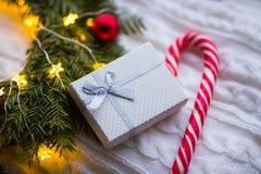 Wit giftdoos en karamelriet dichtbij sparkroon met rode Kerstmisballen en gerold met gloeiende slinger met warm licht op wit stock foto's