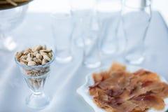 Wit glas pistaches op lijst met lege bierglazen op bedelaars royalty-vrije stock foto