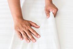 Wit het bedblad van de handopstelling in hotelruimte Stock Foto