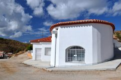 Wit hol-huis en blauwe hemel met wolken stock fotografie
