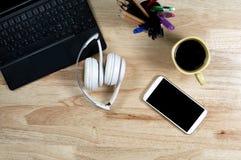 Wit hoofdtelefoons en toetsenbord op de houten lijst stock foto's