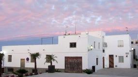 Wit huis en de roze Wolken bij montainstad royalty-vrije stock afbeeldingen