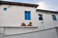 Wit huis met blauwe vensters stock foto's