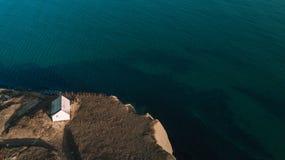 Wit huis op een berg over een klip, over het blauwe overzees stock foto's