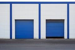 Wit Industrieel pakhuis met blauwe deur voor vrachtwagens stock afbeeldingen