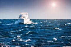 Wit jacht in het rode overzees bij zonsondergang Stock Afbeeldingen
