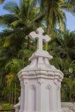 Wit Katholiek kruis op de achtergrond van verse heldergroene palmen onder een duidelijke blauwe hemel royalty-vrije stock afbeeldingen