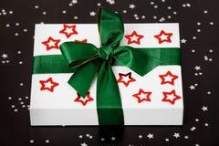Wit Kerstmis huidig vakje met rode sterren en een groen lint, die op een donkere die lijst liggen, door kleine zilveren sterren w Royalty-vrije Stock Afbeelding