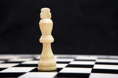 Wit Koning en schaakbord op een zwarte achtergrond Royalty-vrije Stock Foto's