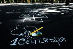 Wit krijt op zwarte asfaltinschrijving in Russisch 1 September gele lijn, kleurrijke tellers, geschilderde ballen, hinkelspels stock illustratie