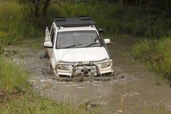 Wit Mazda BT-50 die 4x4 3L modderige vijver kruisen Stock Foto