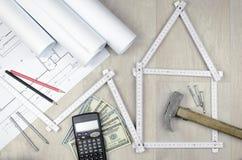 Wit meterhulpmiddel die een huis en techniekhulpmiddelen op houten vormen Royalty-vrije Stock Foto