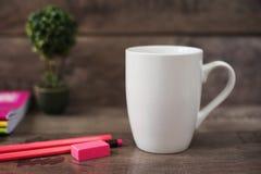 Wit mokmodel Lege mok Het model van de koffiemok met helder neon kleurt potloden en notitieboekjes Ingemaakte installatiebonsai e Royalty-vrije Stock Foto's