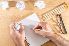 Wit notastootkussen op een houten lijst Rond de blocnotes ligt partij verfrommeld document royalty-vrije stock afbeelding