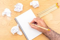 Wit notastootkussen op een houten lijst Rond de blocnotes ligt partij verfrommeld document stock afbeeldingen