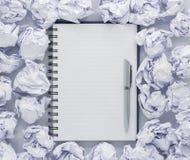 Wit notastootkussen op witte achtergrond Rond de blocnotes ligt partij verfrommeld document, Exemplaarruimte stock foto's