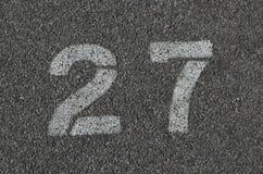 Wit 27 op teer wordt geschilderd die stock afbeeldingen
