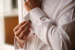 Wit overhemd met twee handen van een witte mens Stock Foto