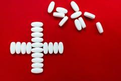 Wit pillenkruis op rode achtergrond stock afbeelding