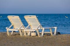 Wit, plastiek sunbeds bij gouden uur op zandig strand van Zakynthos, Griekenland stock fotografie