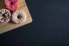 Wit, roze en bruin verglaasd donuts in linkerkant op zwarte houten achtergrond royalty-vrije stock afbeeldingen
