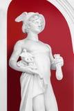 Wit Standbeeld van de God Hermes op een geschilderde rode muurachtergrond Stock Foto